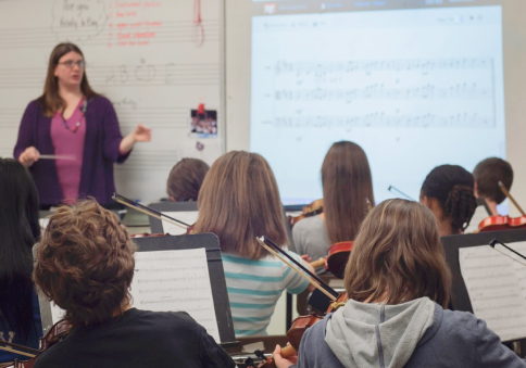 Educator in front of music class